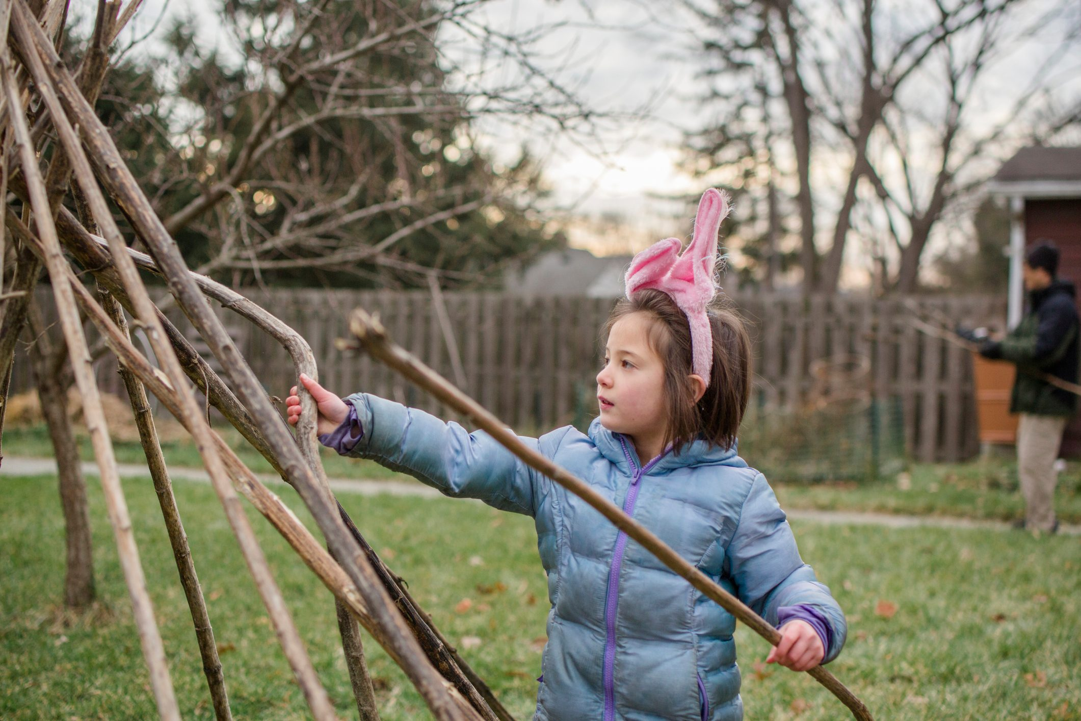 A little girl in bunny ears and jacket builds fort with father in yard