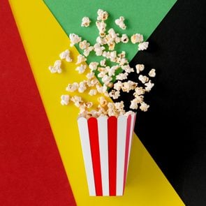 movie popcorn spilled out on a red, yellow, green, and black background for black history month