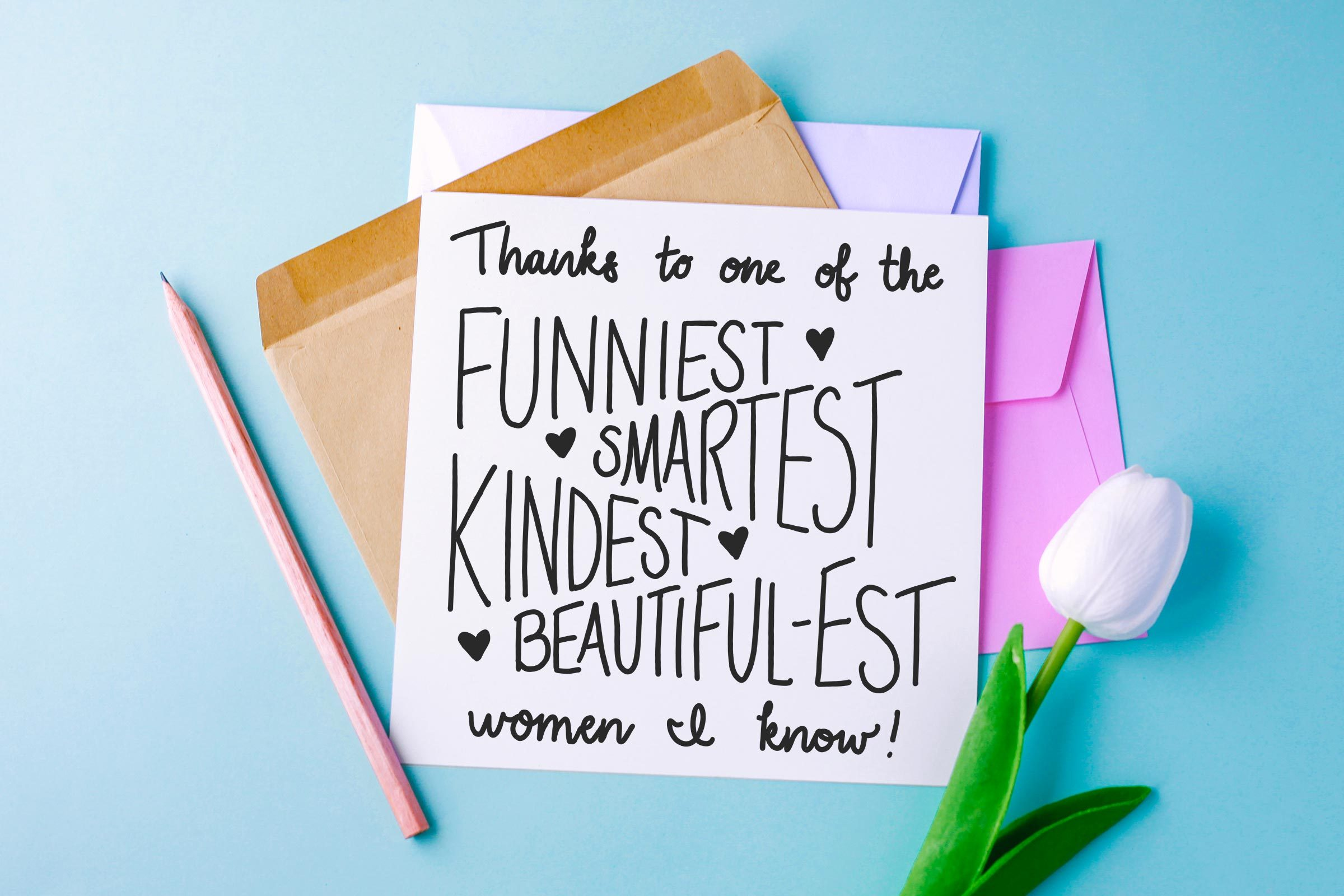 """stack of cards, pencil, and white tulip on blue background. top card reads, """"thanks to one of the funniest, smartest, kindest, beautiful-est women i know!"""""""
