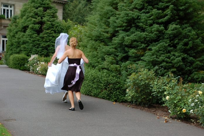 A bride running with her bridesmaid