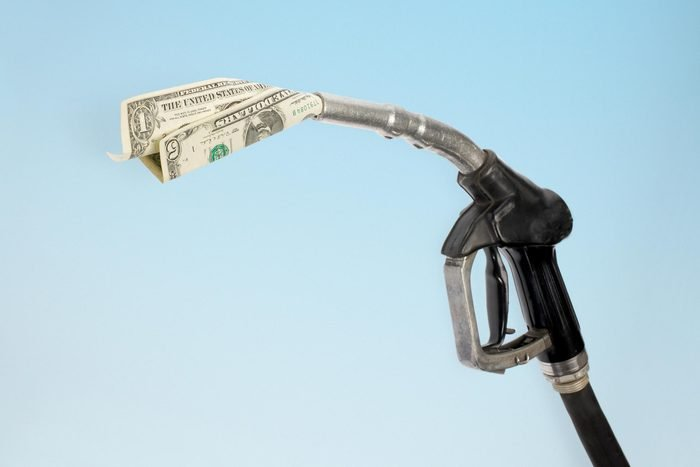 gas pump with a one dollar bill and a five dollar bill coming out of the end of the pump
