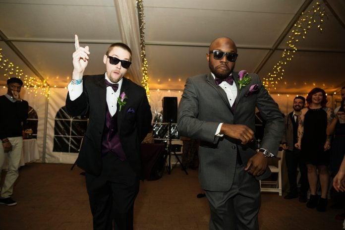 Groom and groomsman dancing at reception
