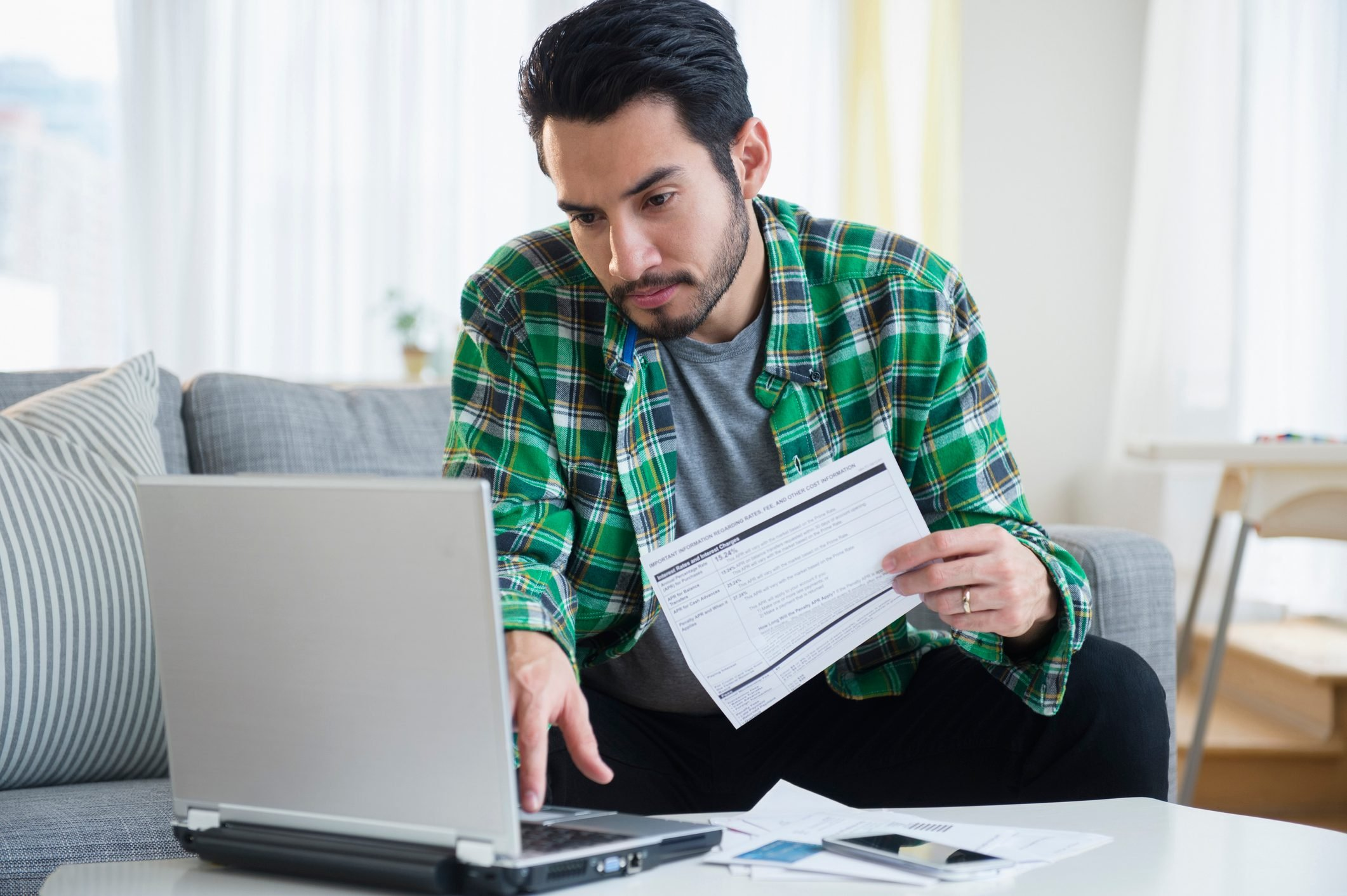 Mixed race man paying bills in living room