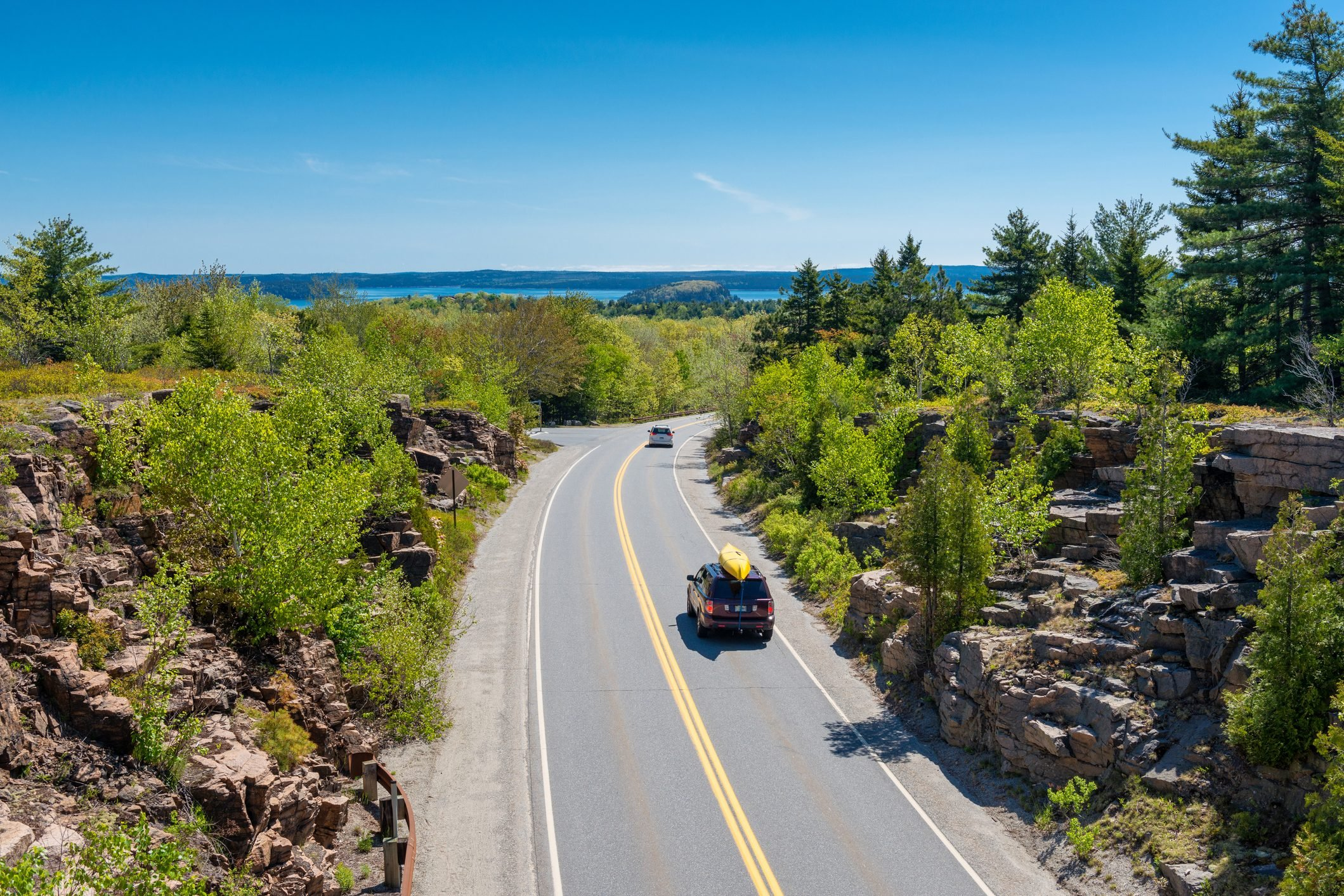Cars driving on road in Acadia National Park, Maine, USA. One car holds a canoe on its roof.