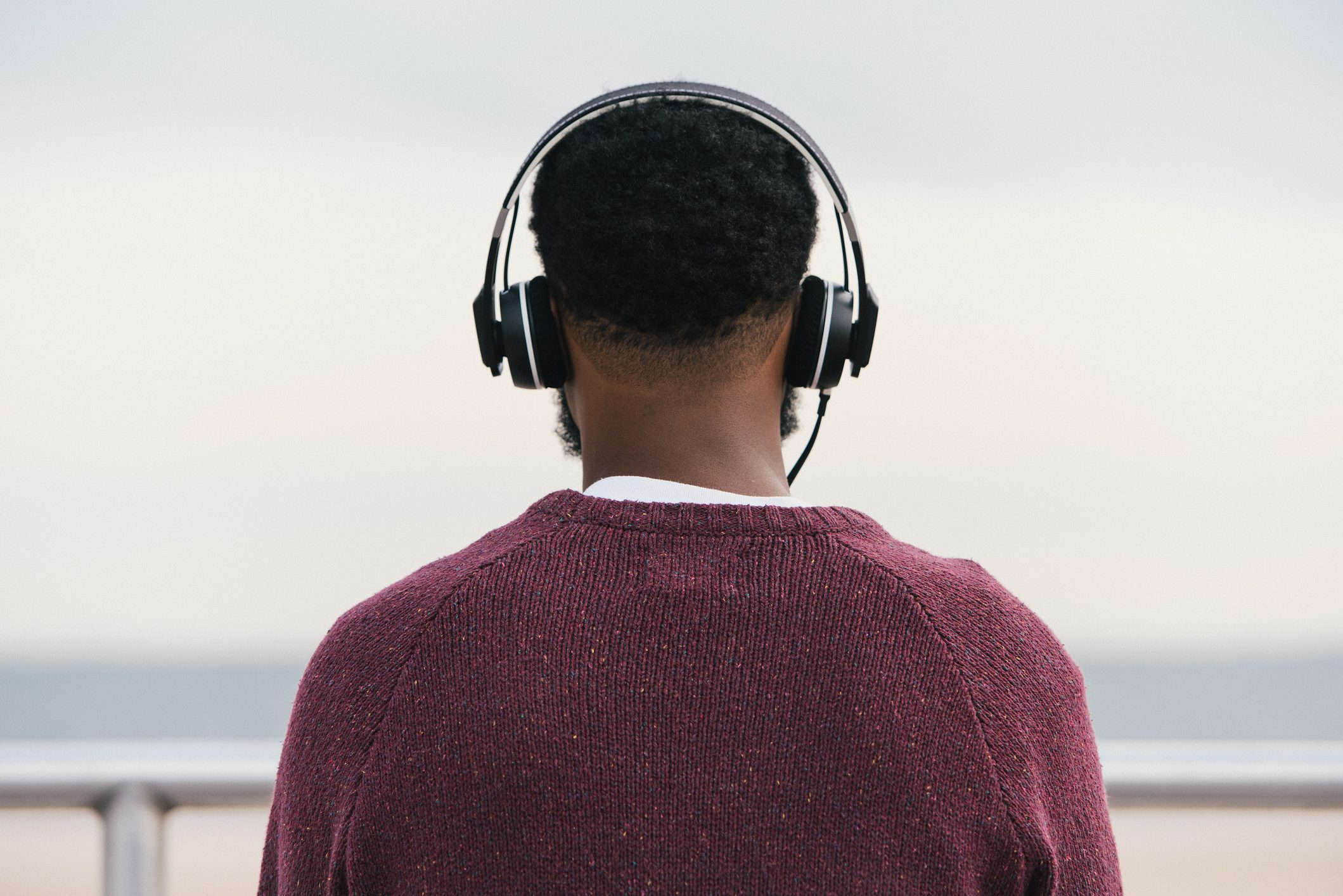 Rear view of man listening to headphones at beach, Coney Island, New York, USA