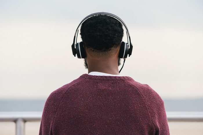 Rear view of man listening to headphones at beach, Coney Island, New York, USA