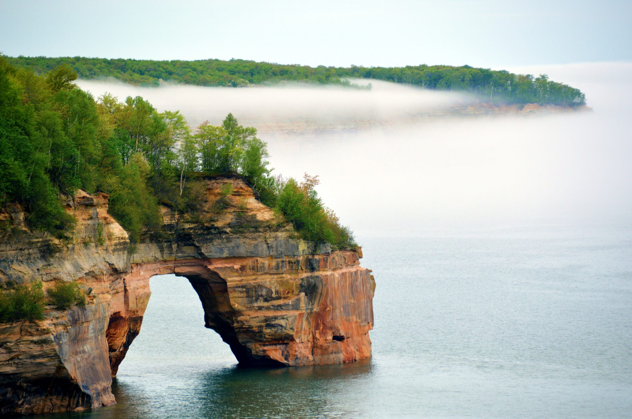 One of the arches along Pictured Rocks National Lakeshore in Michigan's Upper Peninsula with mist in the background