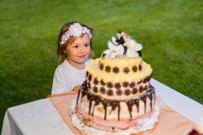 Sweet little girl looking up at a wedding cake