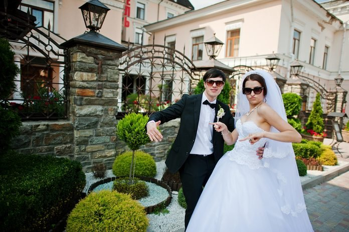wedding couple with dark glasses and striking funny poses