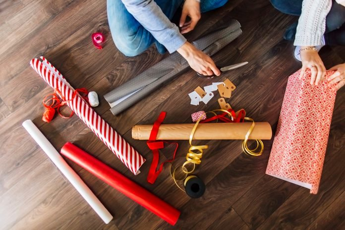 Cropped image of man and woman wrapping gifts at home