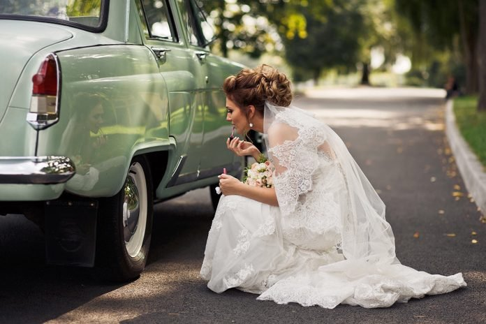 Side View Of Bride Applying Lipstick By using a car as mirror