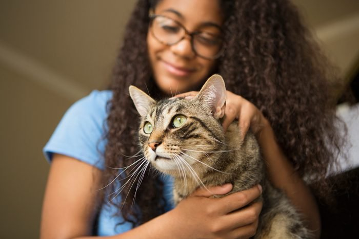 A girl with a pet cat on her lap.