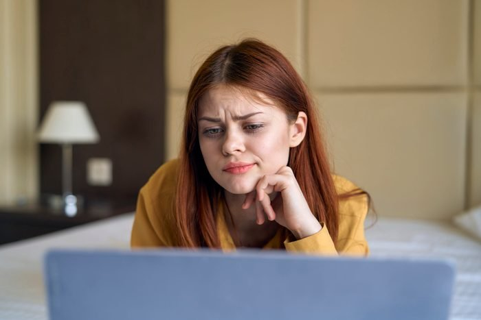 Confused Caucasian woman laying on bed using laptop