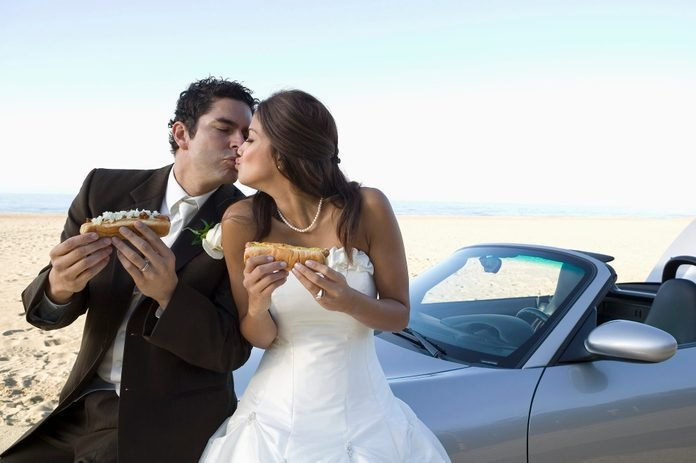 newlyweds kissing while holding hotdogs and posing by thier convertible on the beach