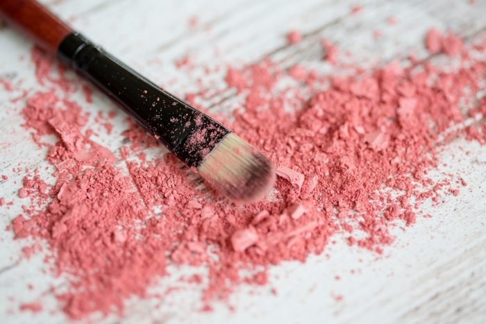 Close-up of a makeup brush laying in crushed cosmetics