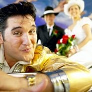 elvis impersonator close to the camera with bride and groom in the background