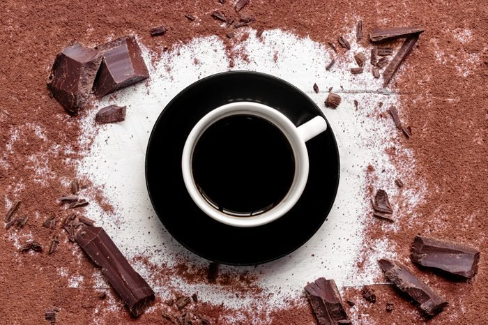 mug of brewed cacao surrounded by ground cacao and chunks of chocolate