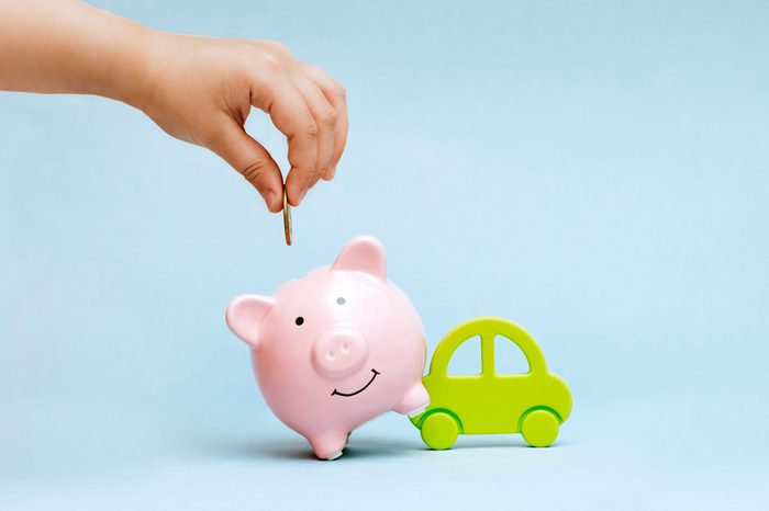 hand adding a coin to a piggy bank leaning on a toy car