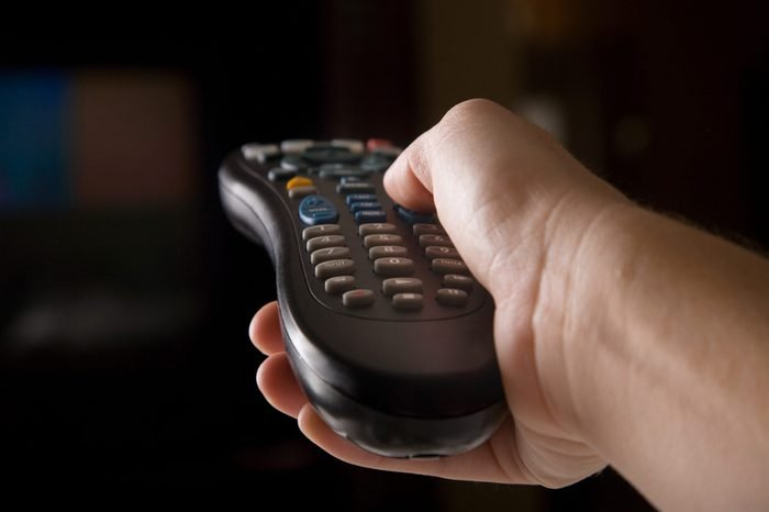 A hand holding a remote to change channels
