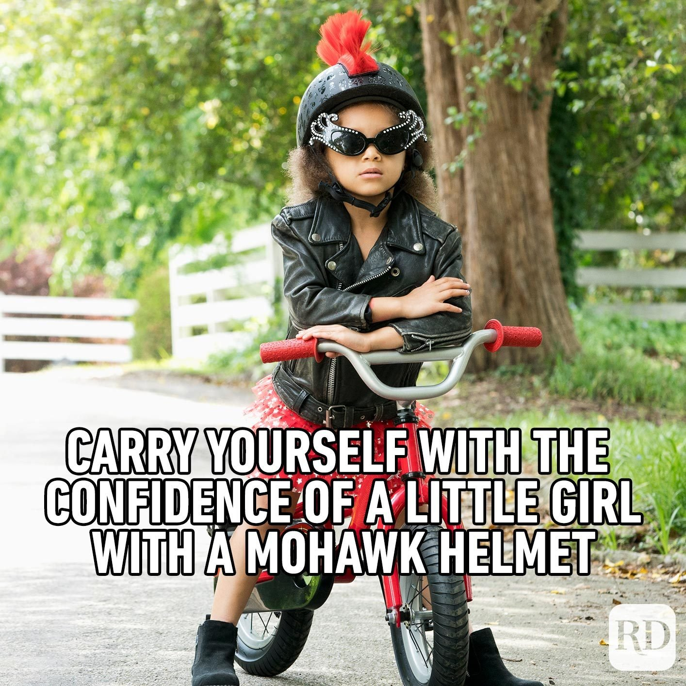 Young girl on a bike with a mohawk helmet. Meme text: Carry yourself with the confidence of a little girl with a mohawk helmet