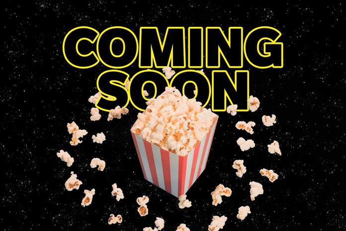 """""""Coming Soon"""" in a Star Wars-like type treatment with a carton of popcorn and popcorn pieces floating in a circle like an asteroid ring"""