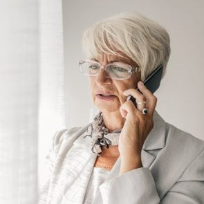 Serious senior woman talking on phone