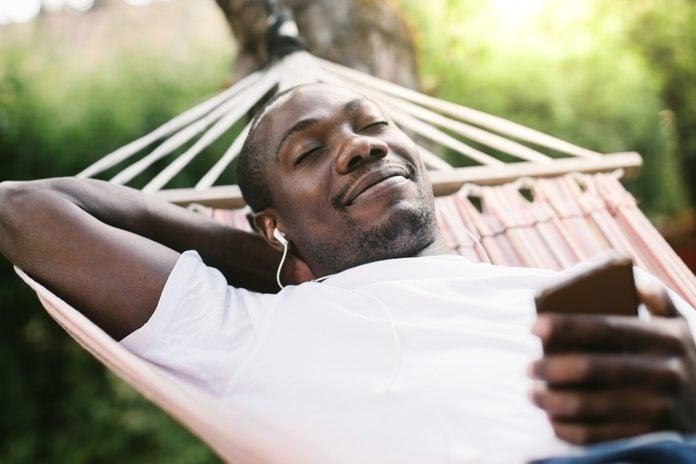 Smiling man with closed eyes enjoying music through mobile phone while relaxing on hammock