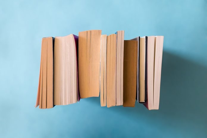 Close-Up Of Stacked Books Against Colored Background