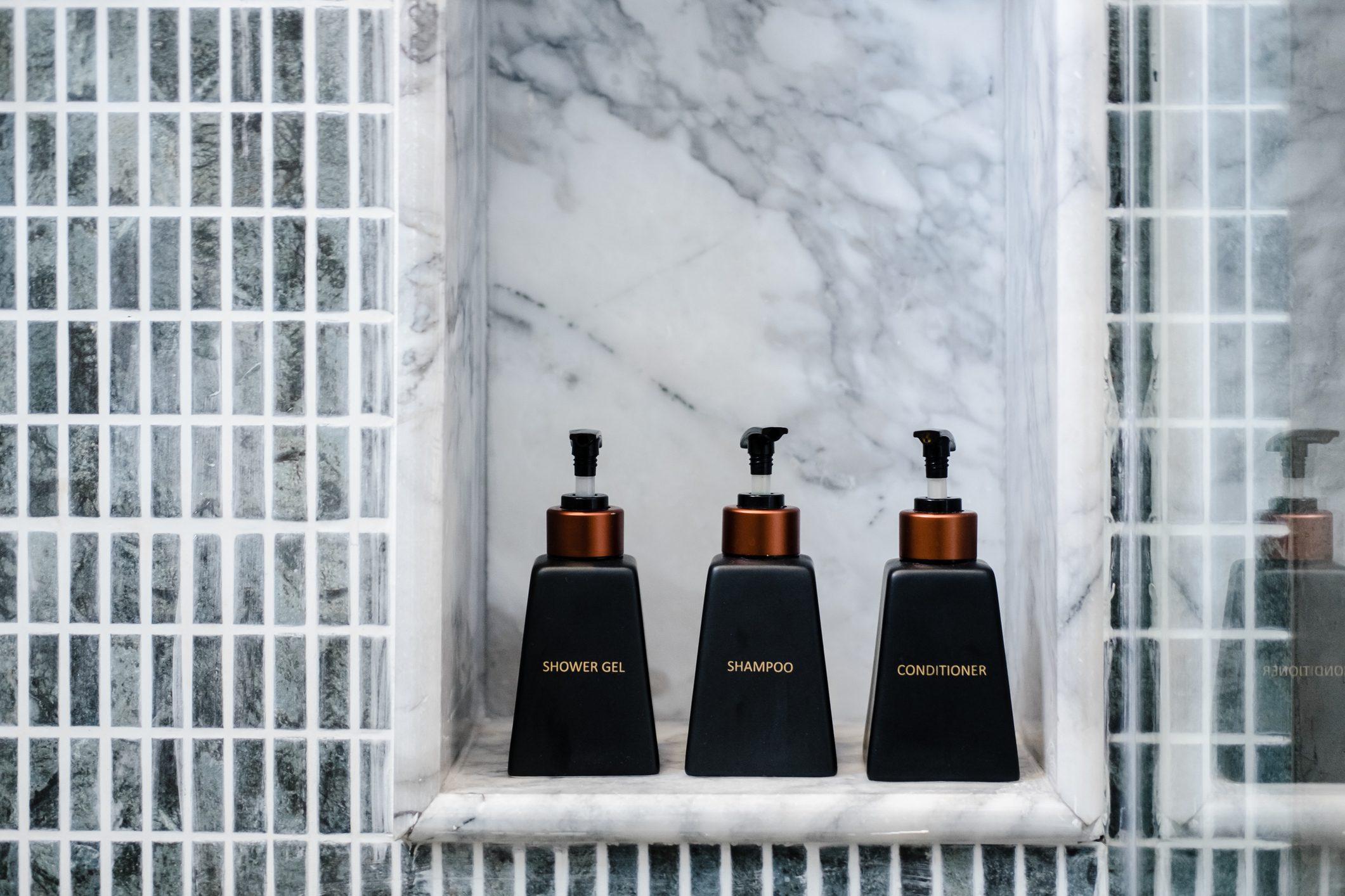 Bathroom toiletries on marble shelf in a hotel shower