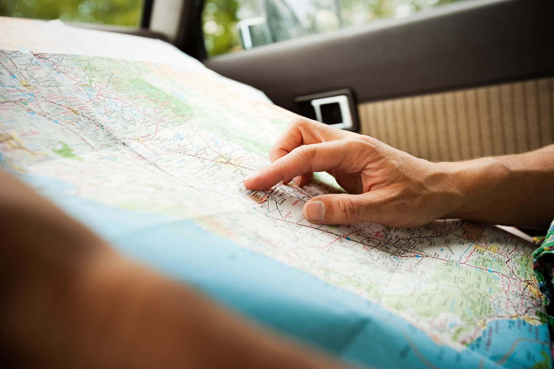 close up of hands examing a map in the car