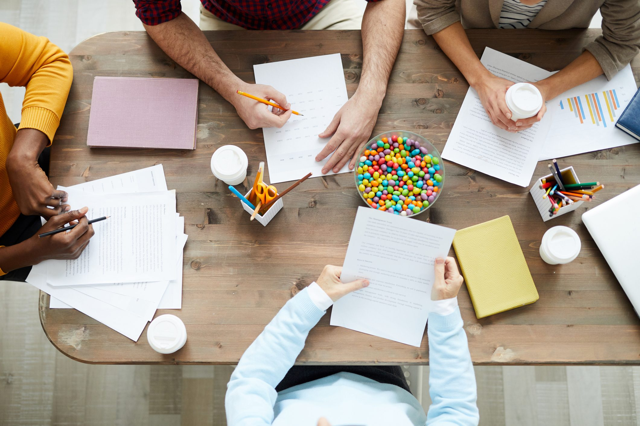 Directly above view of marketing specialists sitting at wooden table with papers and candies and discussing reports and charts