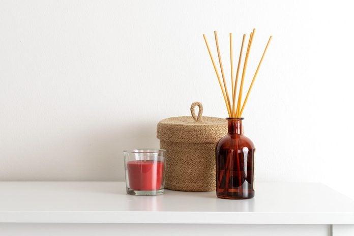Scandinavian nordic hygge style, home interior - candle, scent aroma diffuser, small straw basket, white shelf