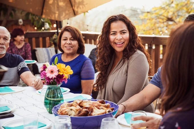 Family laughing together during outdoor dinner party