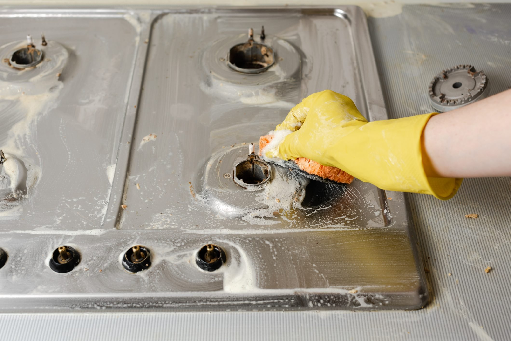Hand in yellow rubber glove wash gas stove burner