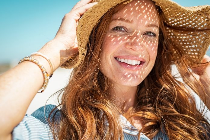 Happy woman on beach wearing straw hat