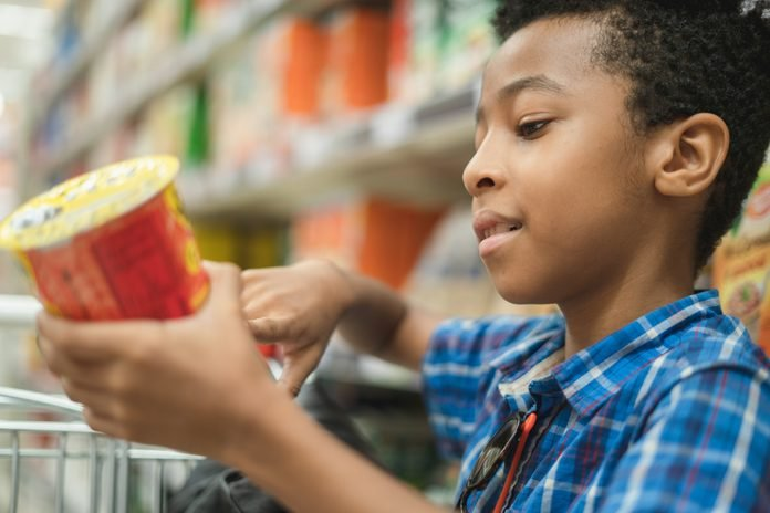 Side View Of Boy Shopping In Supermarket