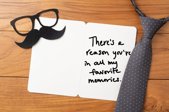 "open father's day card on wood backgroung with tie and mustache prop; card reads, ""There's a reason you're in all my favorite memories"" in handwriting"