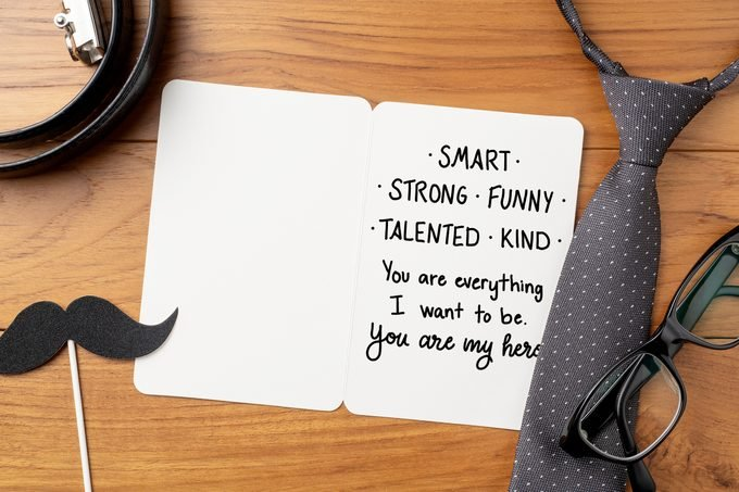 "open father's day card on wood background with tie, belt, glasses, and mustache prop; card reads, ""smart, strong, funny, talented, kind: you are everything i want to be. you are my hero"" in handwriting"
