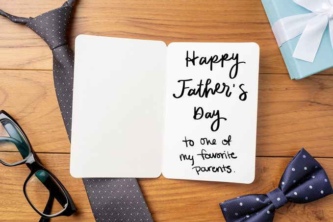 "open father's day card on wood background with tie, glasses, bowtie, and gift; card reads, ""Happy father's day to one of my favorite parents"" in handwriting"