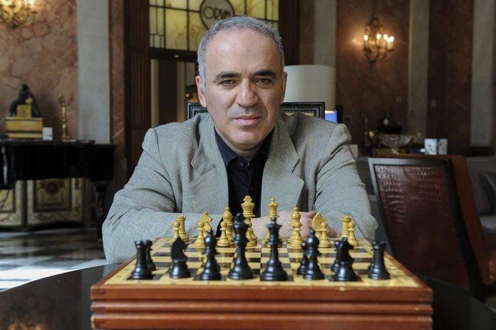 Garry Kasparov sitting with a chess board