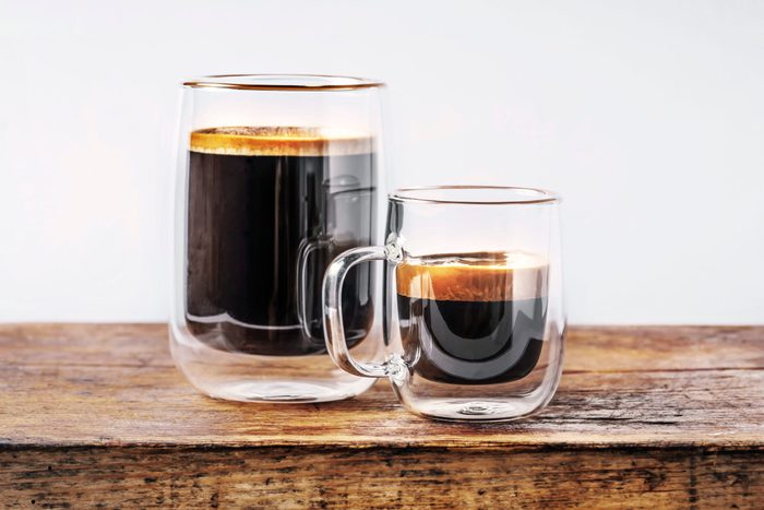 two clear mugs on a wooden surface; the large mug contains coffee, the smaller mug contains espresso