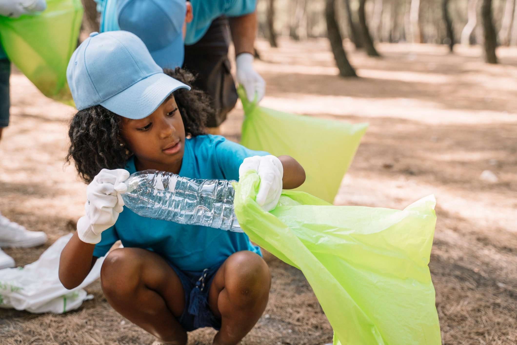 Group of volunteering children collecting garbage in a park