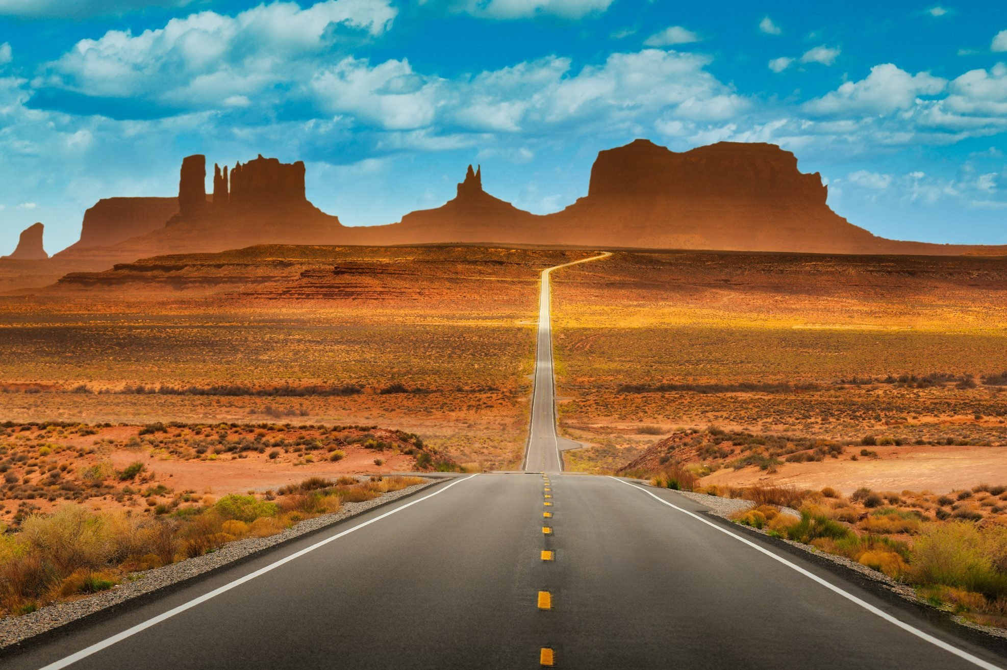 View of historic U.S. Route 163 running through famous Monument Valley in beautiful golden evening light at sunset on a beautiful sunny day with blue sky in summer, Utah, USA