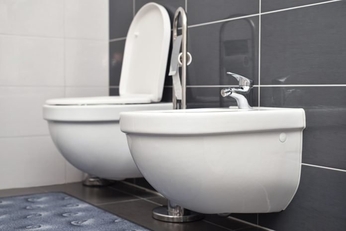 White bidet and toilet attached to a gray wall in the bathroom