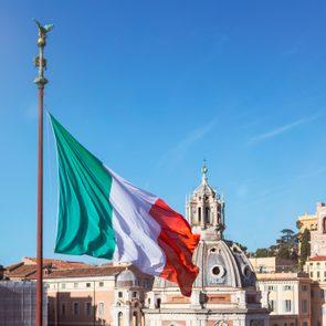 Italy, Rome, Italian flag fluttering against clear blue sky and dome of Santa Maria di Loreto