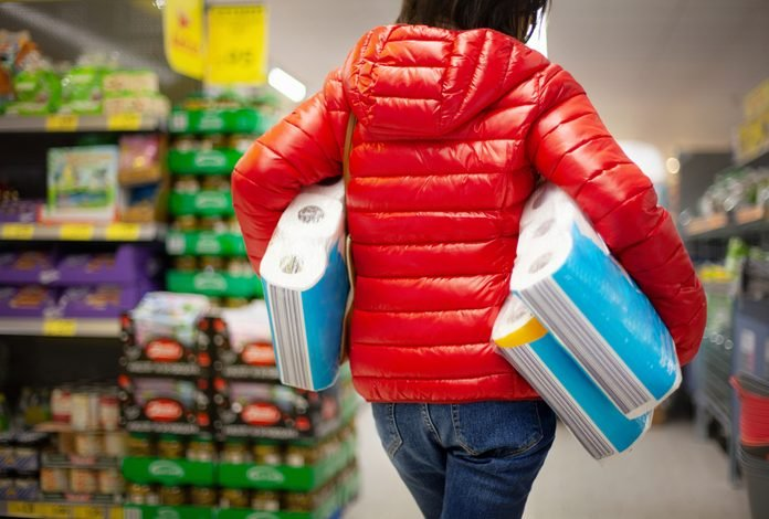 Woman at the supermarket, buying paper towels in abundance for lack of toilet paper