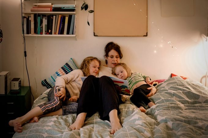 Full length of mother reading picture book while sitting with children in bedroom