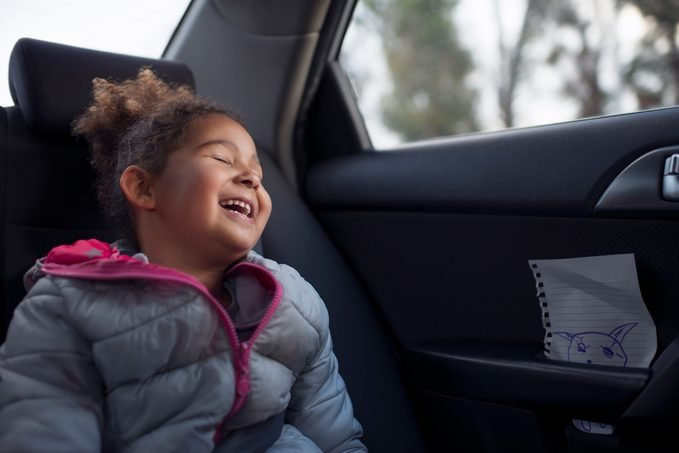 Happy excited passenger child girl traveling on the rear vehicle seat.