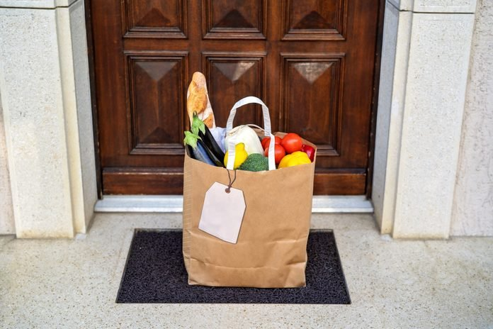 Contactless food delivery service concept. Paper bag with groceries delivered and left outside at entrance door. Online shopping. Healthy fresh fruit and vegetables, zero waste, recyclable package.