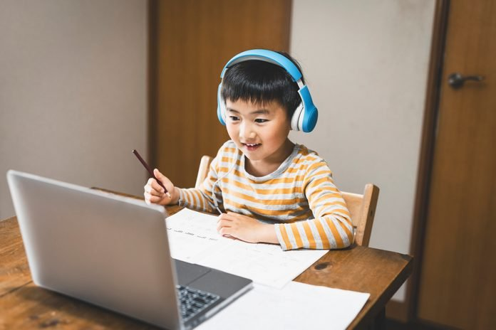 Boy wearing headset taking an e-Learning course with laptop